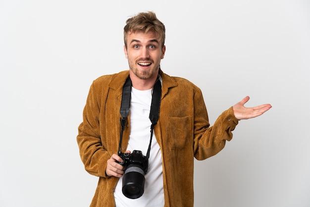 Молодой фотограф блондин мужчина изолирован с шокированным выражением лица