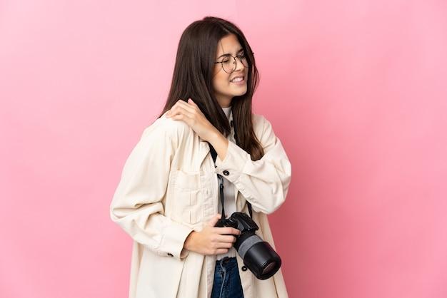 努力したために肩の痛みに苦しんでピンクに孤立した若い写真家ブラジルの女の子