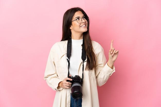 素晴らしいアイデアを指しているピンクの壁に分離された若い写真家ブラジルの女の子