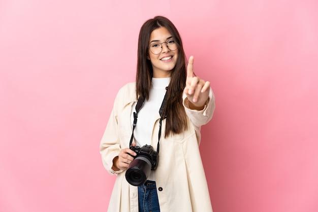 ピンクの壁に隔離された若い写真家ブラジルの女の子が指を見せて持ち上げる