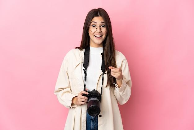 Молодой фотограф бразильская девушка изолирована на розовой стене удивлена и указывает вперед