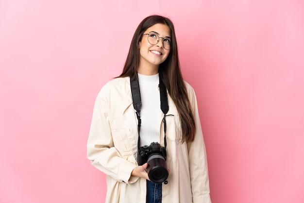見上げながらアイデアを考えてピンクの壁に孤立した若い写真家ブラジルの女の子