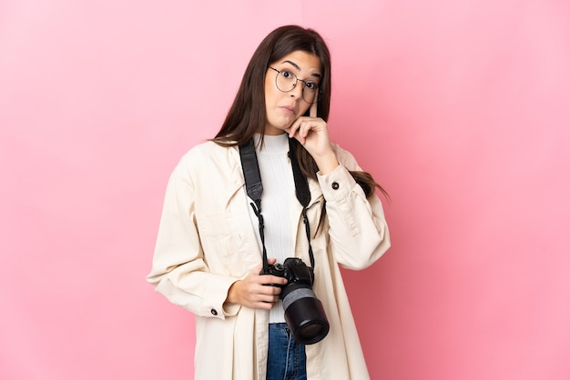 Молодой фотограф бразильская девушка изолирована на розовой стене, думая об идее