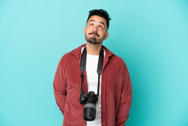 Молодой фотограф кавказский человек изолирован на синем фоне и смотрит вверх