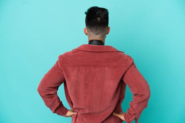 Молодой фотограф кавказский человек изолирован на синем фоне в заднем положении