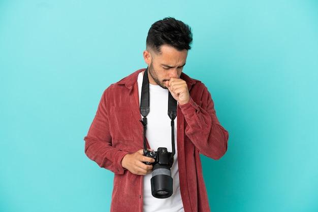 Молодой фотограф кавказский мужчина изолирован на синем фоне страдает от кашля и плохо себя чувствует