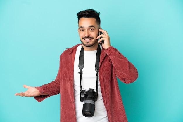 Молодой фотограф кавказский человек изолирован на синем фоне, разговаривая с кем-то по мобильному телефону