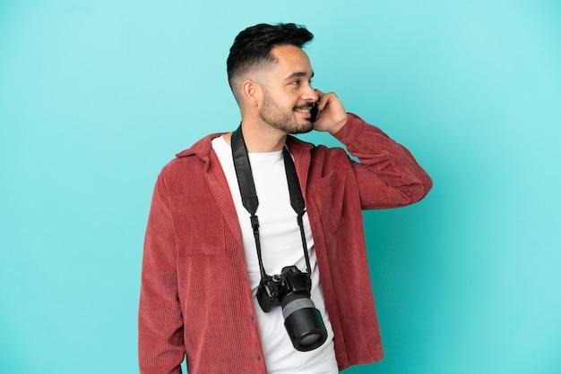 携帯電話との会話を維持している青い背景に分離された若い写真家白人男性