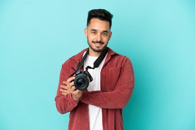 Молодой фотограф кавказский человек изолирован на синем фоне, держа скрещенными руками в фронтальном положении