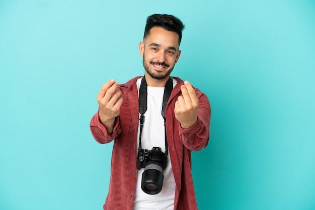 Молодой фотограф кавказский человек изолирован на синем фоне, делая денежный жест
