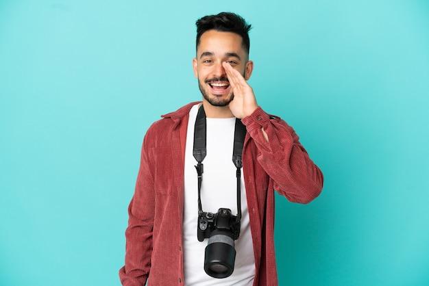 Молодой фотограф кавказский человек изолирован на синем фоне кричит с широко открытым ртом