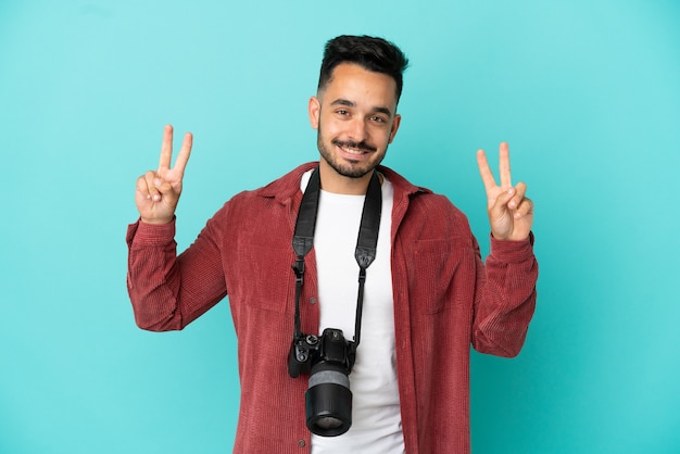 Молодой фотограф кавказский человек изолирован на синем фоне показывает знак победы обеими руками