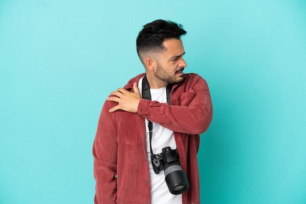 Молодой фотограф кавказский человек изолирован на синем фоне страдает от боли в плече за то, что приложил усилие