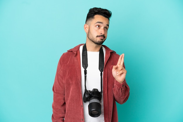 Молодой фотограф кавказский человек изолирован на синем фоне со скрещенными пальцами и желает лучшего