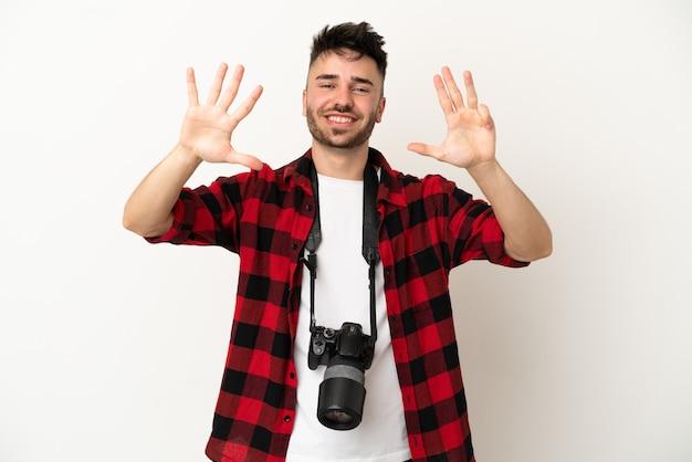 Молодой фотограф кавказский человек изолирован на белом фоне, считая девять пальцами
