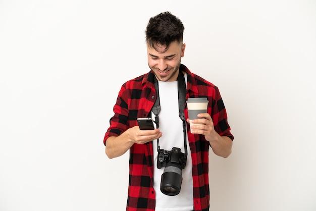 Молодой фотограф кавказский человек, изолированные на белом фоне, держа кофе на вынос и мобильный