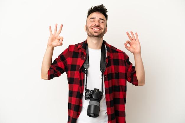 Молодой фотограф кавказский человек изолирован на белом фоне в позе дзен