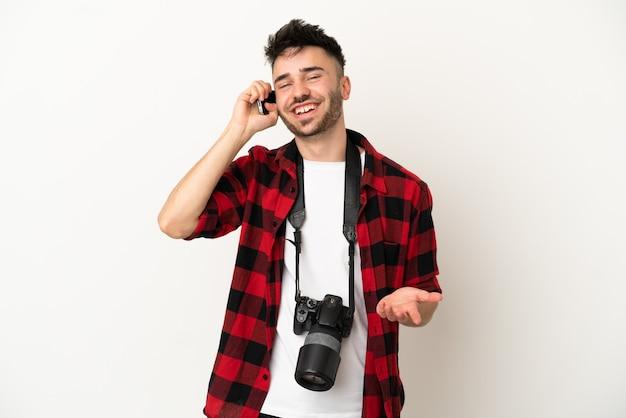 Молодой фотограф кавказский человек, изолированные на белом фоне, разговаривает по мобильному телефону с кем-то