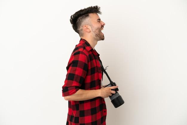 Молодой фотограф кавказский человек, изолированные на белом фоне, смеясь в боковом положении