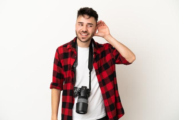 Молодой фотограф кавказский человек изолирован на белом фоне, слушая что-то, положив руку на ухо