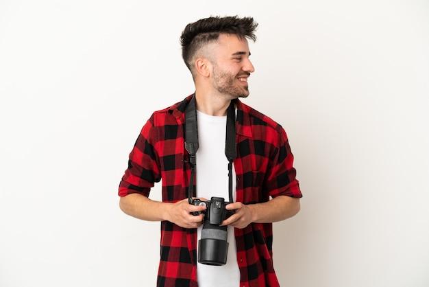 Молодой фотограф кавказский человек изолирован на белом фоне смотрит сторону