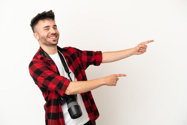 Молодой фотограф кавказский человек изолирован на белом фоне, указывая пальцем в сторону и представляя продукт