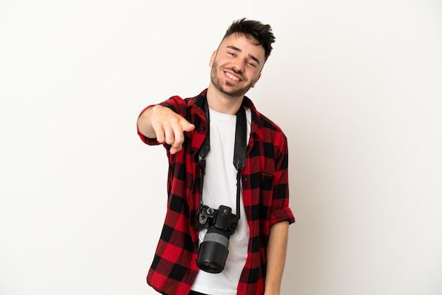 Молодой фотограф кавказский мужчина на белом фоне указывает пальцем на вас с уверенным выражением лица