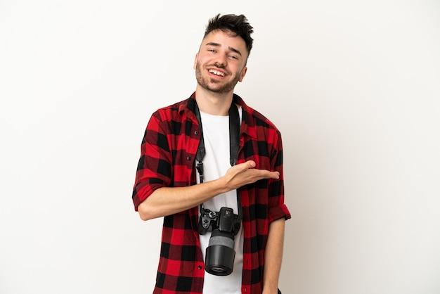 Молодой фотограф кавказский человек, изолированные на белом фоне, представляя идею, глядя в сторону