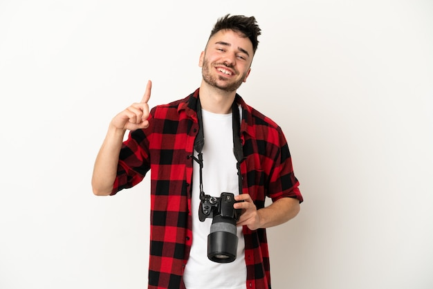 Молодой фотограф кавказский человек изолирован на белом фоне, показывая и поднимая палец в знак лучших