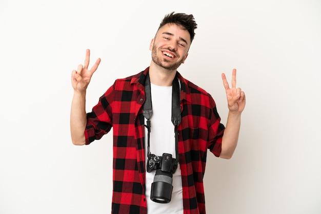 Молодой фотограф кавказский человек изолирован на белом фоне показывает знак победы обеими руками
