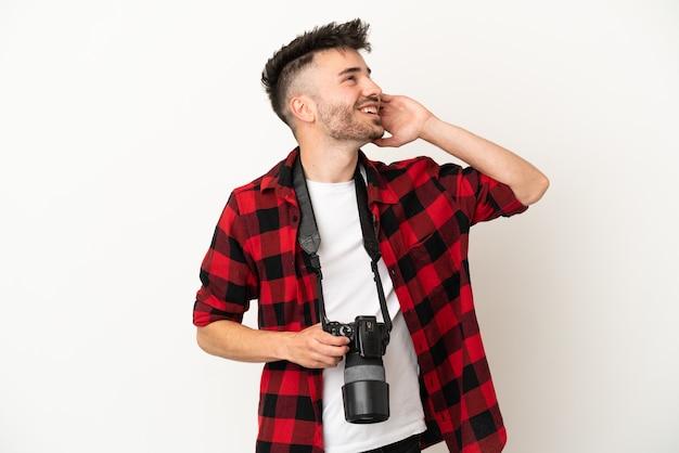 Молодой фотограф кавказский человек изолирован на белом фоне, думая об идее