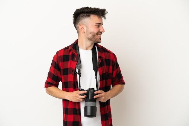Молодой фотограф кавказский человек изолирован на белом фоне со скрещенными руками и счастлив