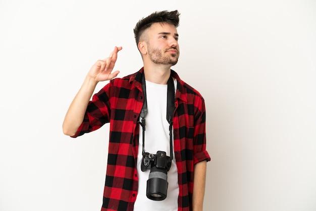 Молодой фотограф кавказский человек изолирован на белом фоне со скрещенными пальцами и желает лучшего