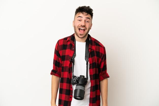 Молодой фотограф кавказский мужчина изолирован на белом фоне с удивленным выражением лица
