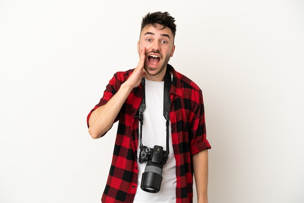 Young photographer caucasian man isolated on white background with surprise and shocked facial expression