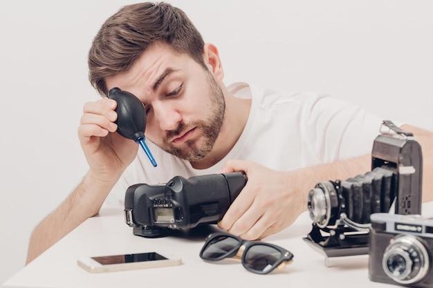Молодой фотограф чистит камеру с вакуумным насосом. ручной пылесос для камеры и объективов. мягкий свет