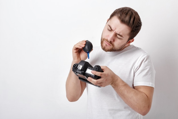 Молодой фотограф чистит камеру с вакуумным насосом. ручной пылесос для камеры и объективов.