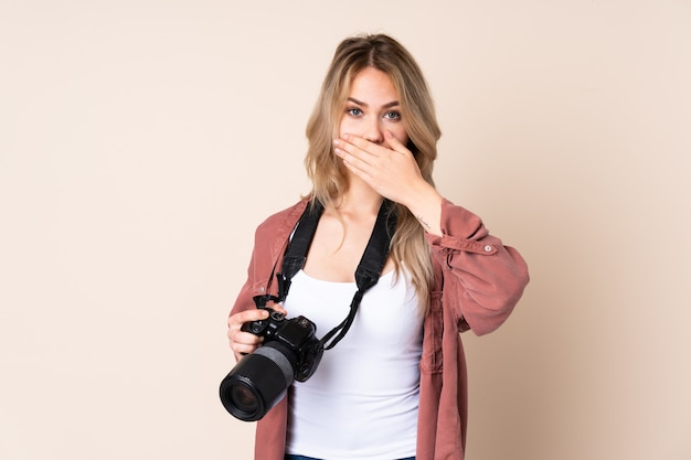 Young photographer girl over isolated covering mouth with hands