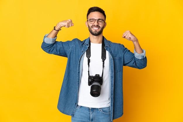 Девушка молодой фотограф изолирована на желтом фоне, делая сильный жест