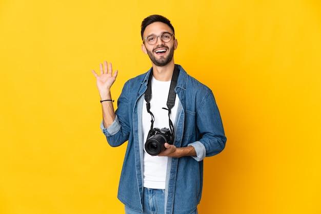 행복 한 표정으로 손으로 경례 노란색 배경에 고립 된 젊은 사진 작가 소녀