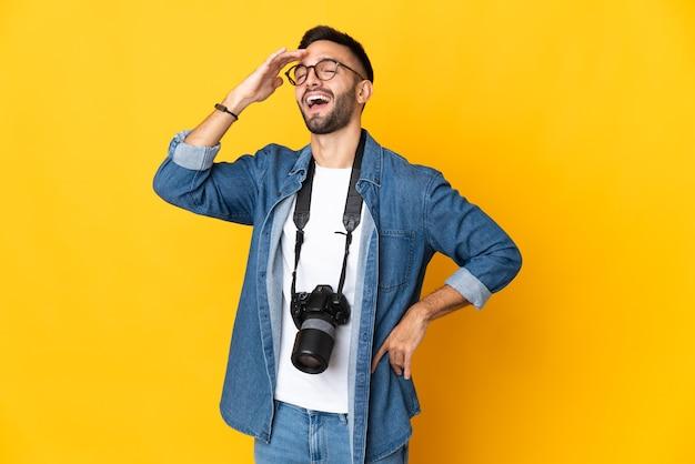 Молодой фотограф девушка изолирована на желтом фоне много улыбается