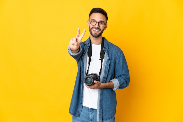 Молодой фотограф девушка изолирована на желтом фоне улыбается и показывает знак победы