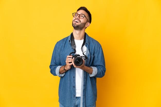 Молодая девушка-фотограф изолирована на желтом фоне, думая об идее, глядя вверх
