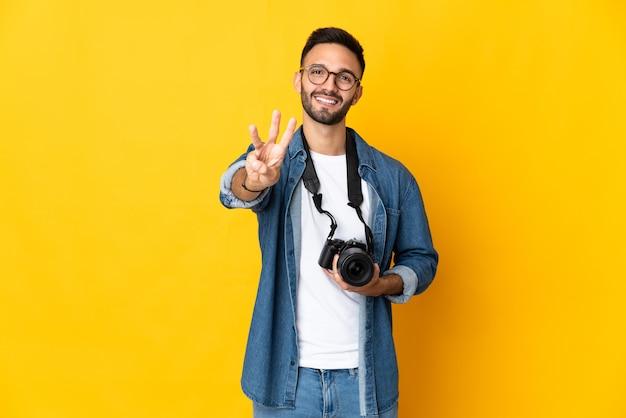 Молодая девушка фотографа изолирована на желтой стене счастлива и считает три пальцами