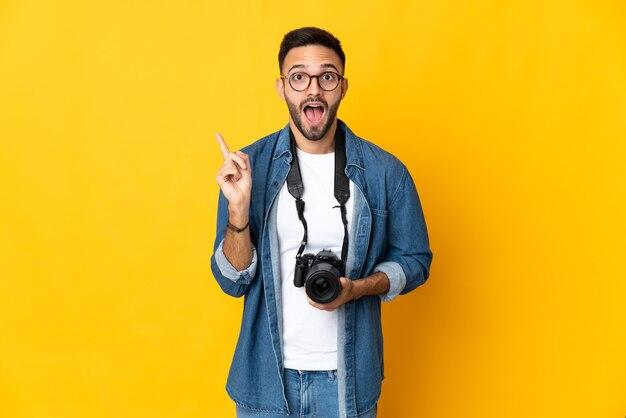 손가락을 들어 올리는 동안 솔루션을 실현하려는 노란색 벽에 고립 된 젊은 사진 작가 소녀
