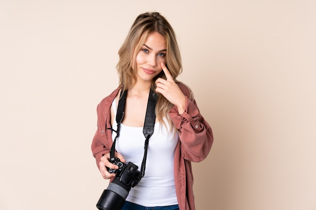 Young photographer girl over isolated showing something