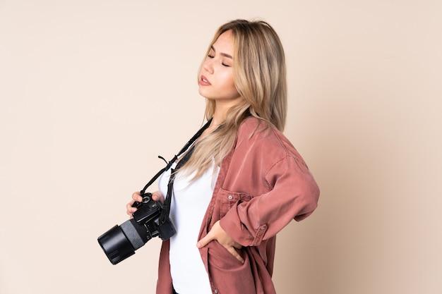 Молодой фотограф девушка страдает от боли в спине из-за того, что приложила усилия