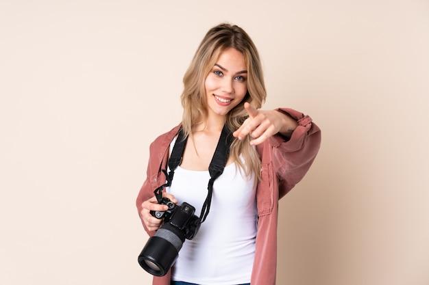 Молодая девушка фотографа над стеной делая жест и указывать телефона