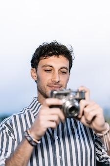 若い写真家がレトロなカメラで写真を撮っています