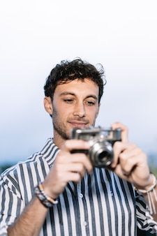 Young photographer is taking a picture with a retro camera